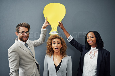 Buy stock photo Studio portrait of three businesspeople standing against a gray background with a cutout lightbulb above their head