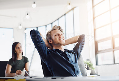 Buy stock photo Shot of a contented designer leaning back in his chair in a modern office