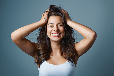 Buy stock photo Studio shot of an attractive young woman posing with her hands in her hair against a blue background