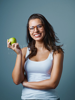 Buy stock photo Studio shot of an attractive young woman holding an apple against a blue background