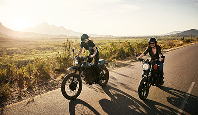 Buy stock photo Shot of two young women riding their motorcycles through the countryside