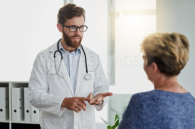 Buy stock photo Cropped shot of a handsome young male doctor talking to a female patient in the hospital