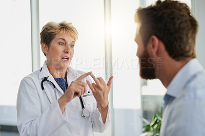 Buy stock photo Cropped shot of an attractive mature female doctor speaking to a male colleague in the hospital