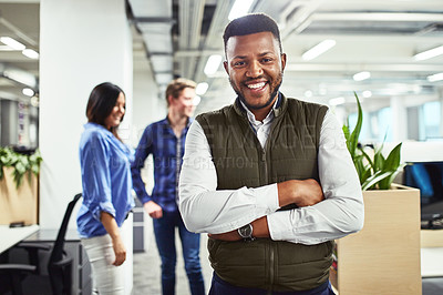 Buy stock photo Portrait of a young designer standing in an office with his colleagues in the background