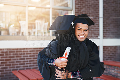 Buy stock photo Shot of two happy young students hugging each other on graduation day