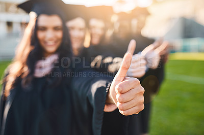 Buy stock photo Closeup shot of two unrecognizable students showing thumbs up on graduation day
