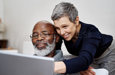 Buy stock photo Shot of an affectionate senior couple using a laptop together while relaxing on the sofa at home