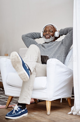 Buy stock photo Shot of a handsome senior man listening to music on a tablet while sitting in his home