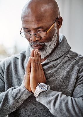 Buy stock photo Shot of a handsome senior man praying in his home