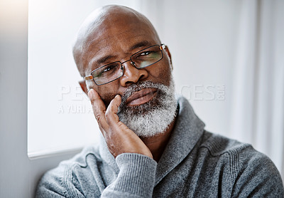 Buy stock photo Shot of a handsome senior man looking thoughtful while sitting in his home