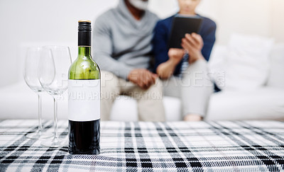 Buy stock photo Shot of an unrecognizable senior couple relaxing on a sofa with their bottle of wine and glasses waiting on a table at home