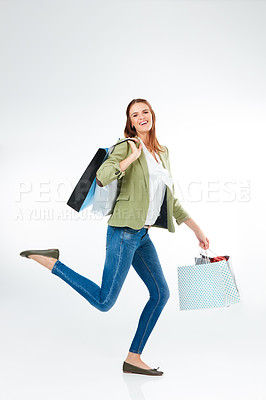 Buy stock photo Studio portrait of a happy young woman carrying shopping bags against a grey background