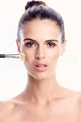 Buy stock photo Cropped shot of a beautiful young woman posing with a makeup brush against a white background
