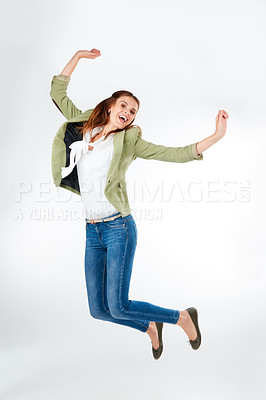 Buy stock photo Studio portrait of a happy young woman jumping for joy against a grey background