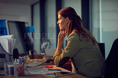 Buy stock photo Shot of a young businesswoman using a computer during a lat night at work