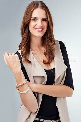 Buy stock photo Studio shot of an attractive young woman modeling fashion-wear against a grey background
