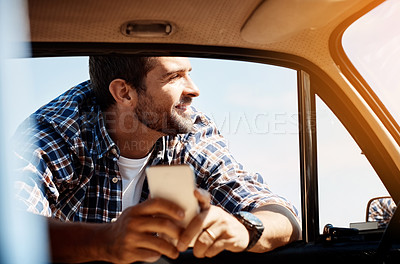 Buy stock photo Cropped shot of a handsome man sending a text while enjoying a road trip
