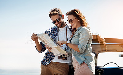 Buy stock photo Cropped shot of an affectionate couple looking at a map while enjoying a road trip
