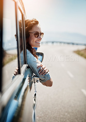 Buy stock photo Cropped shot of an attractive woman hanging out of a car window while enjoying a road trip
