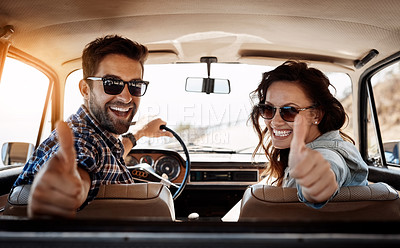 Buy stock photo Rearview portrait of an affectionate couple giving you a thumbs up while enjoying a road trip
