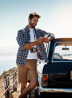 Buy stock photo Shot of a handsome man sending a text while enjoying a road trip