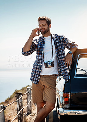 Buy stock photo Shot of a handsome man talking on his cellphone while out on a road trip