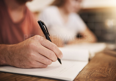 Buy stock photo Cropped shot of two unrecognizable students having a study session at a table in a cafe