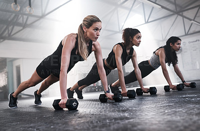 Buy stock photo Shot of a group of fit young women working out with dumbbells at the gym