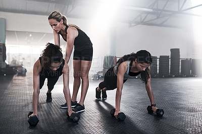 Buy stock photo Shot of young women working out with dumbbells and a trainer at the gym