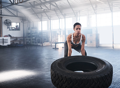 Buy stock photo Shot of young women getting ready to lift a tyre in the gym
