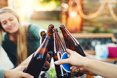 Buy stock photo Shot of a group of young friends holding up drinks and toasting to celebrate their friendship around a table outdoors