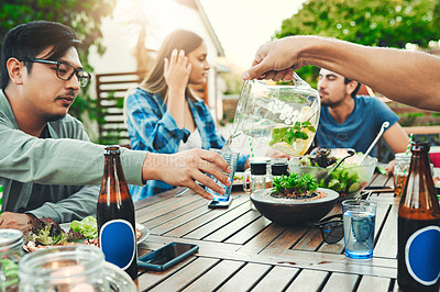 Buy stock photo Shot of two friends pouring water in a glass for each other while sitting around a table in an outdoor gathering amongst friends