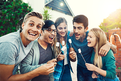Buy stock photo Portrait of a group of young friends posing together and holding up marshmallows on sticks outside