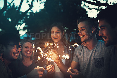 Buy stock photo Shot of a group of cheerful young friends having fun with sparklers together outside in the evening