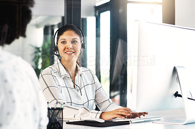 Buy stock photo Shot of a call centre agent talking to her colleague in an office