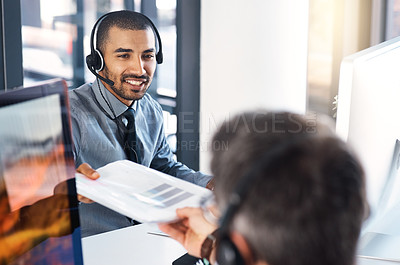 Buy stock photo Shot of a call centre agent passing paperwork to his colleague in an office
