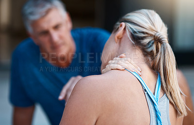 Buy stock photo Shot of a mature woman holding her neck in pain after an intense workout session with her husband
