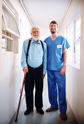Buy stock photo Shot of a young doctor helping his senior patient walk down a hallway in hospital