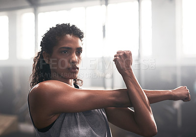 Buy stock photo Shot of a sporty young woman exercising in a gym