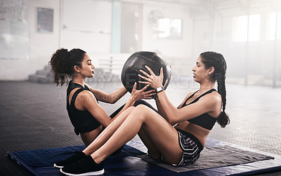 Buy stock photo Shot of two sporty young women working out together with an exercise ball in a gym