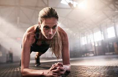 Buy stock photo Shot of a sporty young woman doing plank exercises in a gym