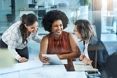 Buy stock photo Shot of a group of businesswomen working on a digital tablet together