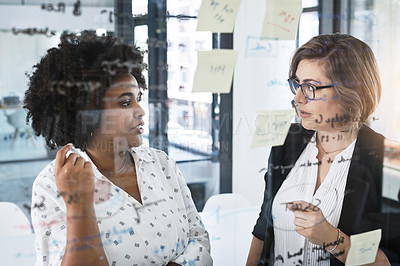 Buy stock photo Shot of two businesswomen brainstorming on a glass wall in an office