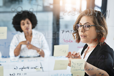 Buy stock photo Shot of a businesswoman presenting notes on a glass wall to her colleague in an office