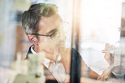 Buy stock photo Shot of a mature businessman brainstorming on a glass wall in an office