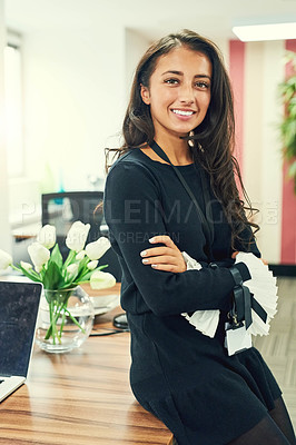 Buy stock photo Cropped portrait of an attractive young businesswoman leaning against her desk in the office