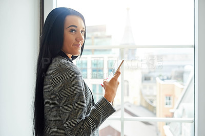 Buy stock photo Cropped portrait of an attractive young businesswoman using her cellphone while standing in the office
