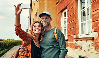 Buy stock photo Cropped shot of a young couple taking a selfie while exploring a foreign city