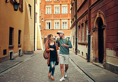 Buy stock photo Shot of a happy young couple taking a walk in a foreign city