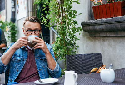 Buy stock photo Cropped shot of a young man having coffee at a sidewalk cafe